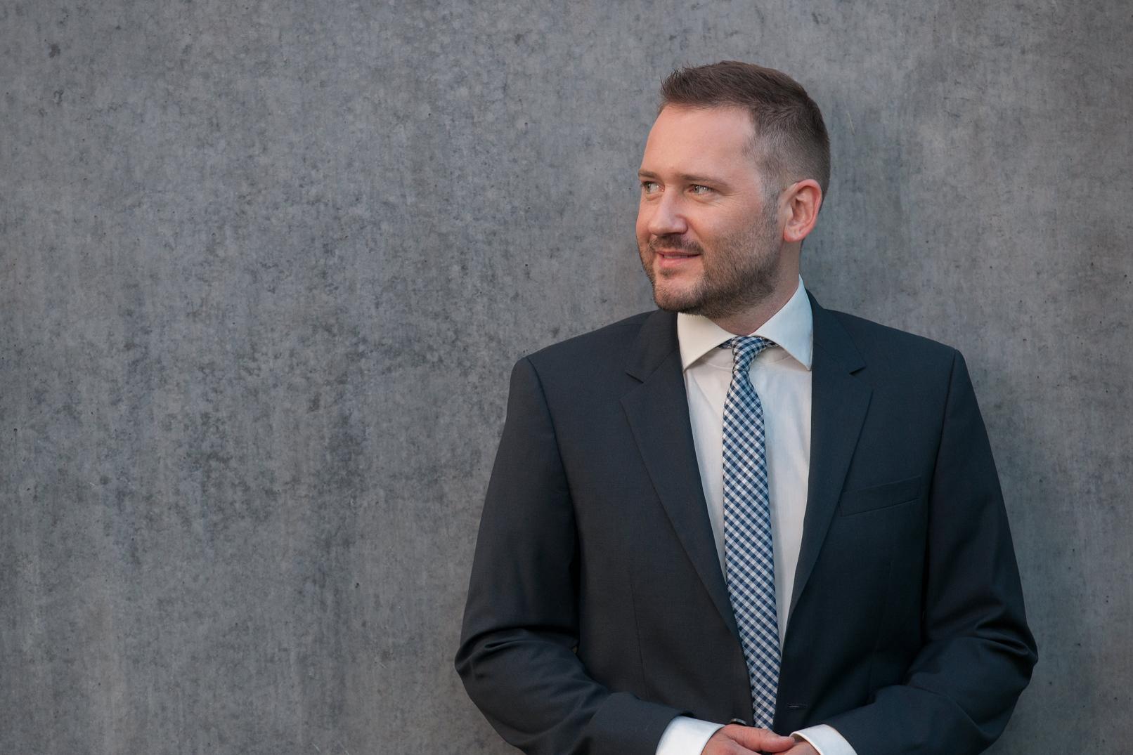 Mann vor grauer Wand beim Shooting eines Business-Portraits