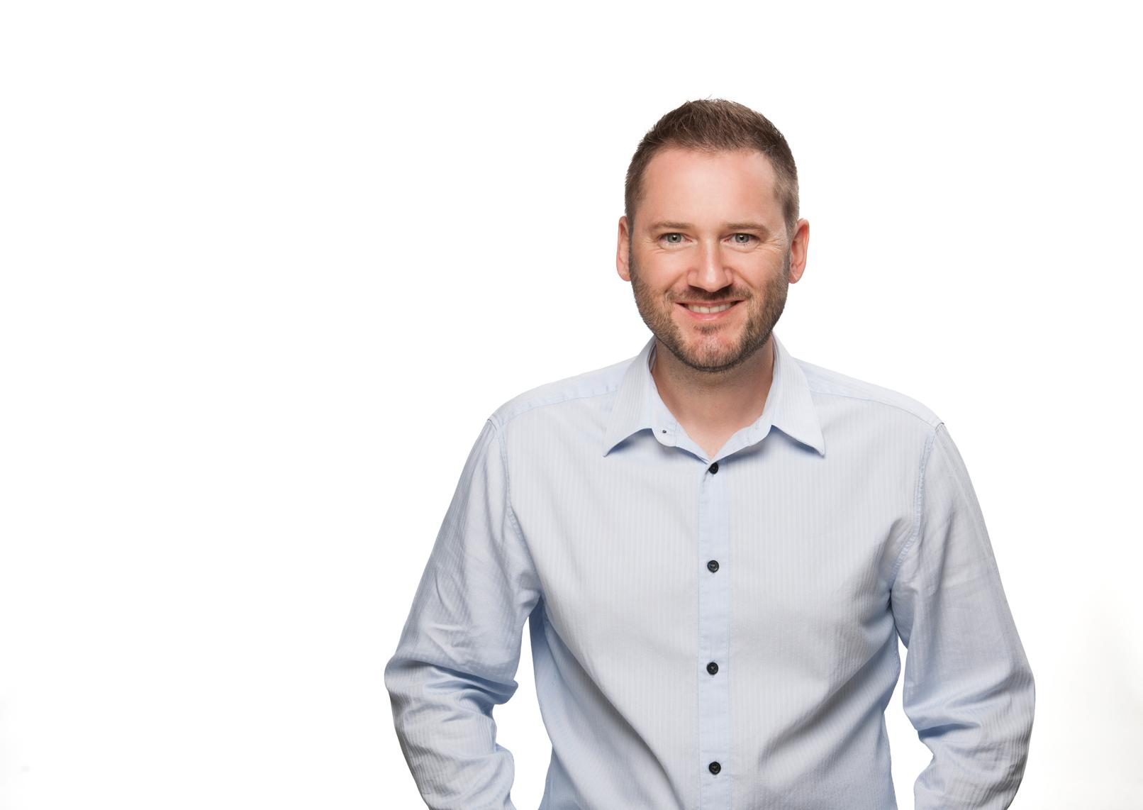 Mann vor weißem Hintergrund beim Shooting eines Business-Portraits
