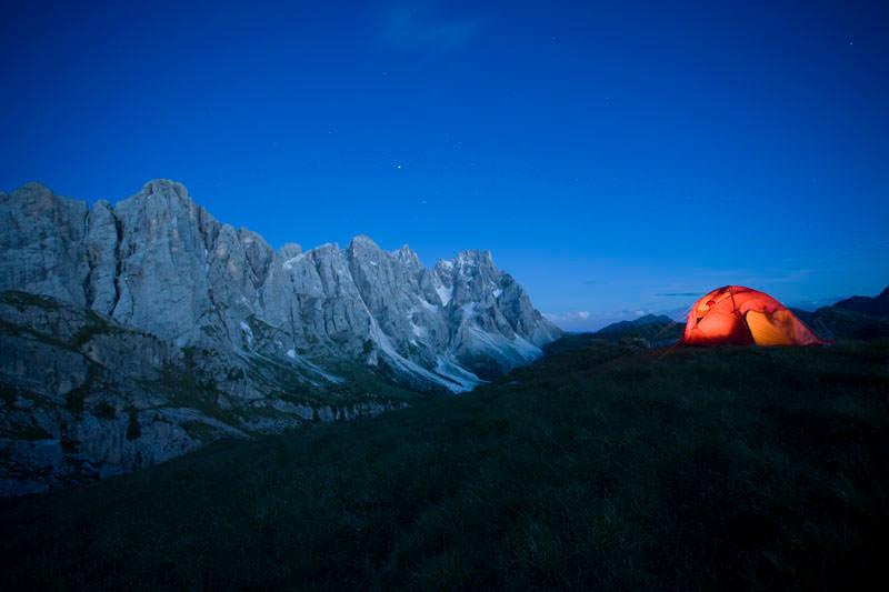 Bergfotografie: Gebirge, davor Zelt auf einer Wiese.