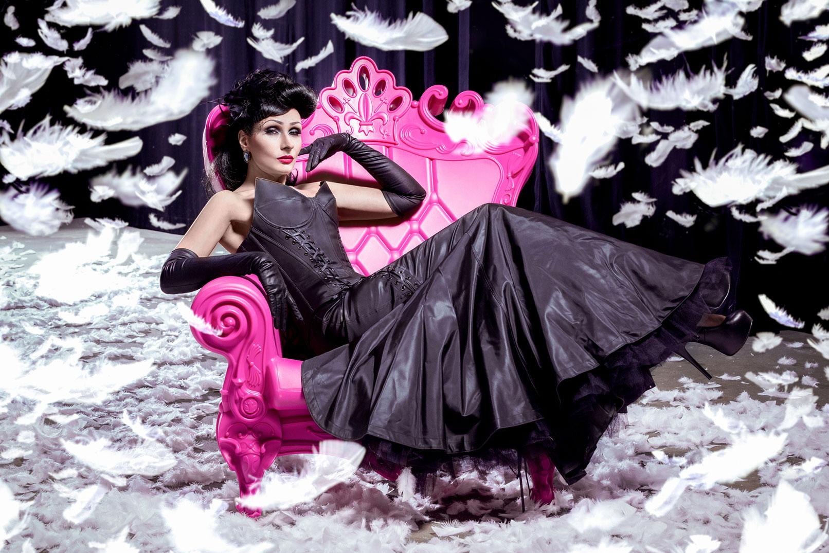 Beispiel zur Beauty-Retusche in Photoshop: Frau auf einem rosa Stuhl, umgeben von fallenden Federn