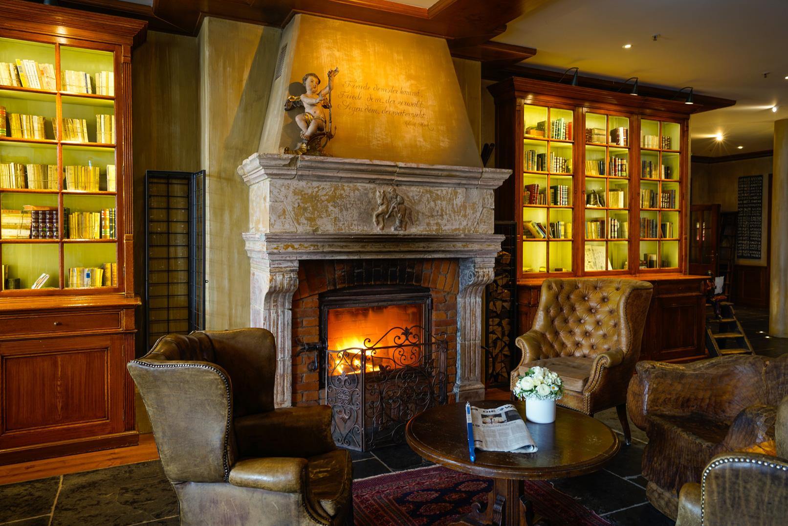 Foto einer Hotelszene mit Kamin, Bücherregal und Sessel