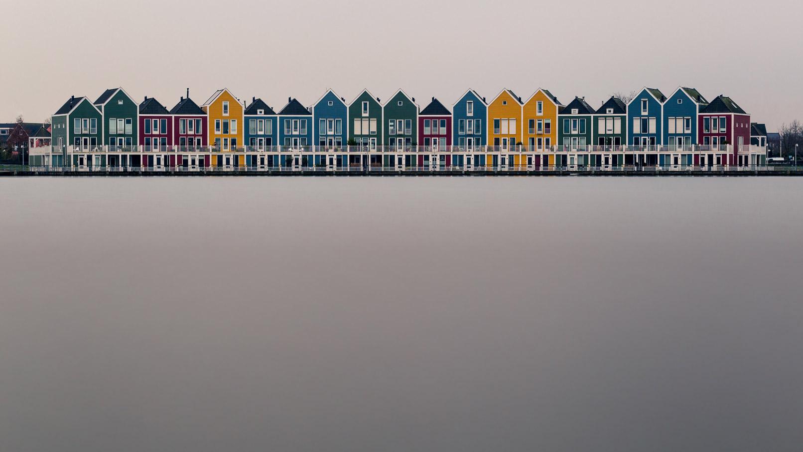 Häuser vor einem See, die Langzeitbelichtung glättet das Wasser
