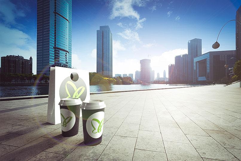 Kaffeebecher und Tüte vor Skyline, erstellt mit Adobe Dimension CC, Beispiel für das Tutorial