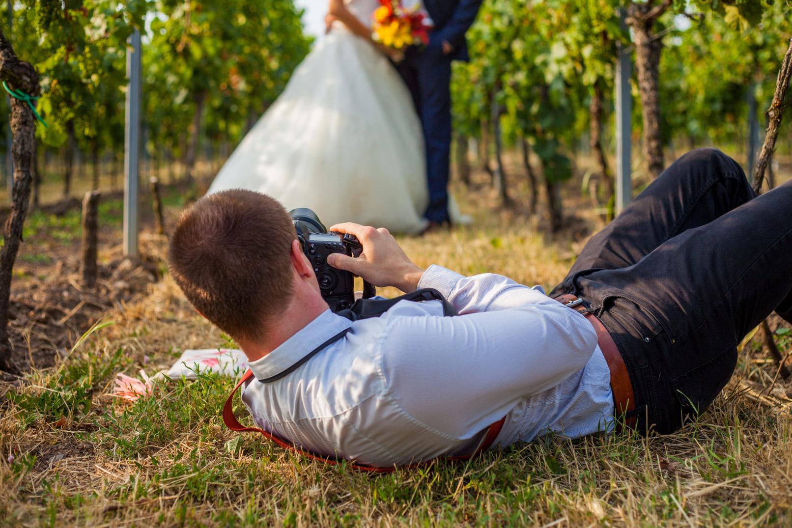 Hochzeitsfotografie: Hochzeitsfotograf auf einer Wiese liegend, um ein Brautpaar zu fotografieren