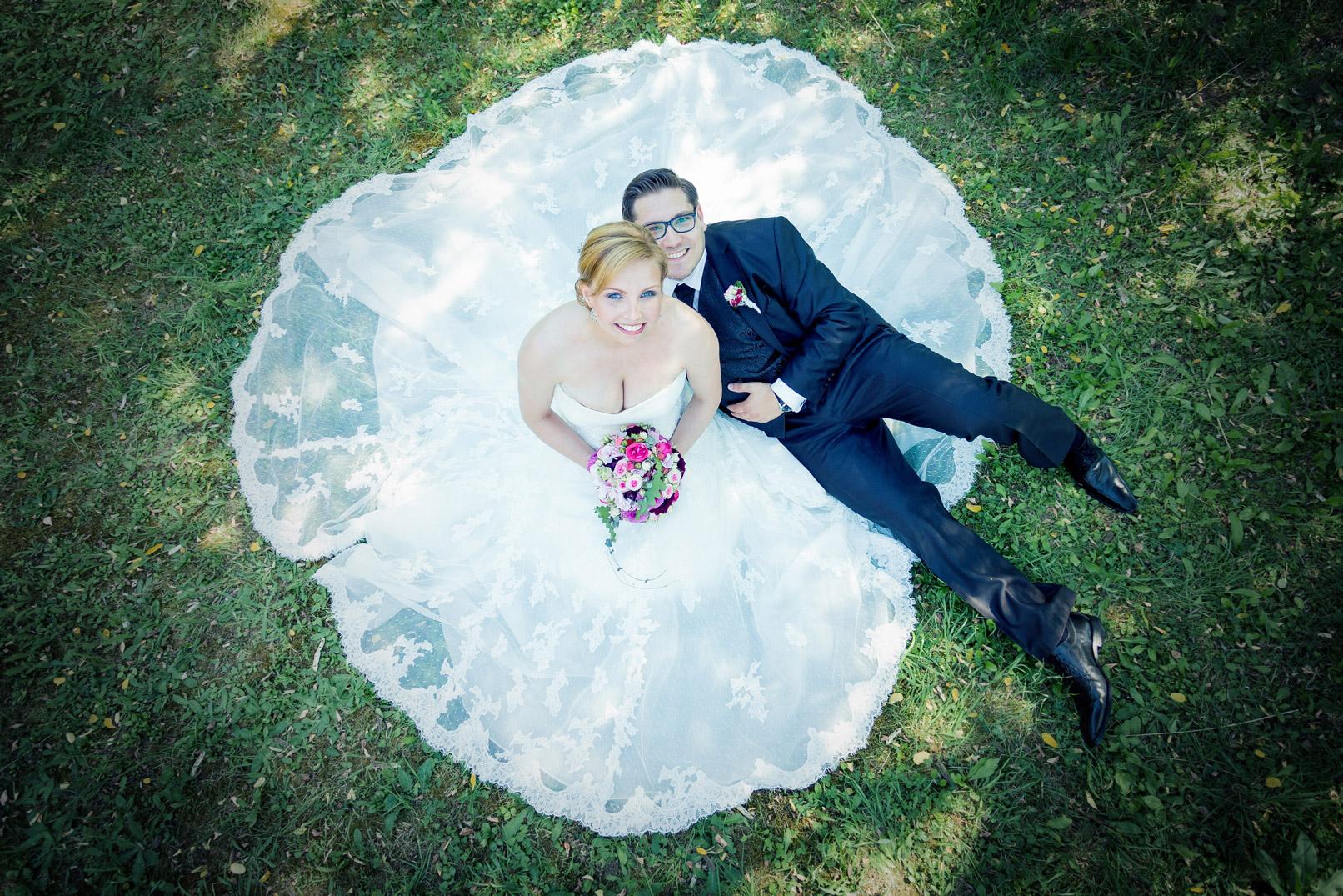 Hochzeitsfotografie: Brautpaar von oben auf einer Wiese fotografiert