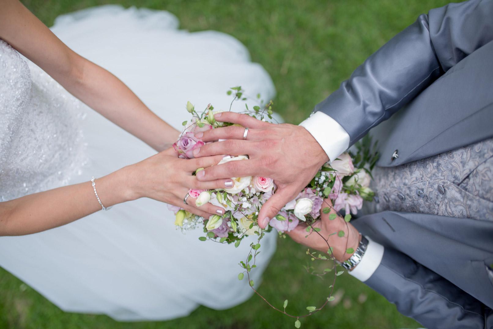 Hochzeitsfotografie: Blick auf einen Blumenstrauß, der vom Brautpaar gehalten wird