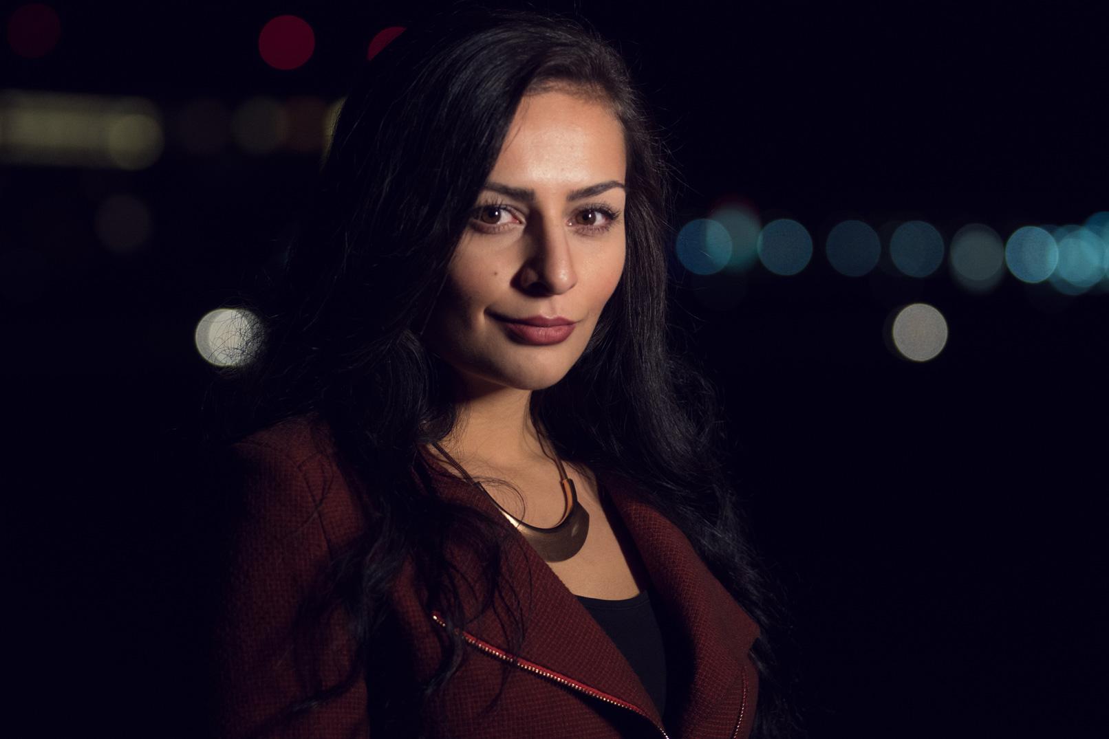 Porträt einer Frau bei Nacht mit Bokehs im Hintergrund.