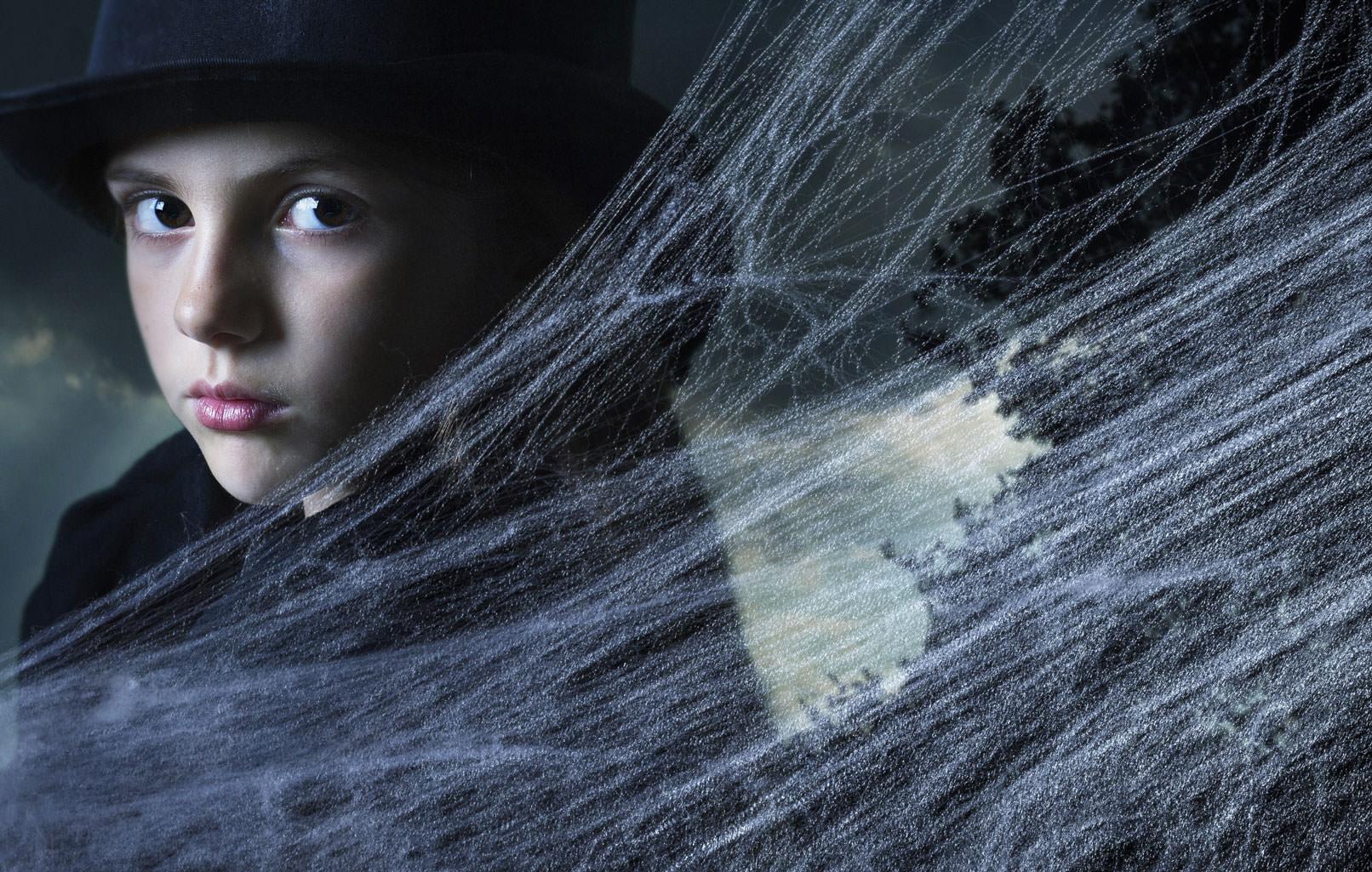 Kind mit schwarzem Hut, davor eingearbeitete Spinnennetze