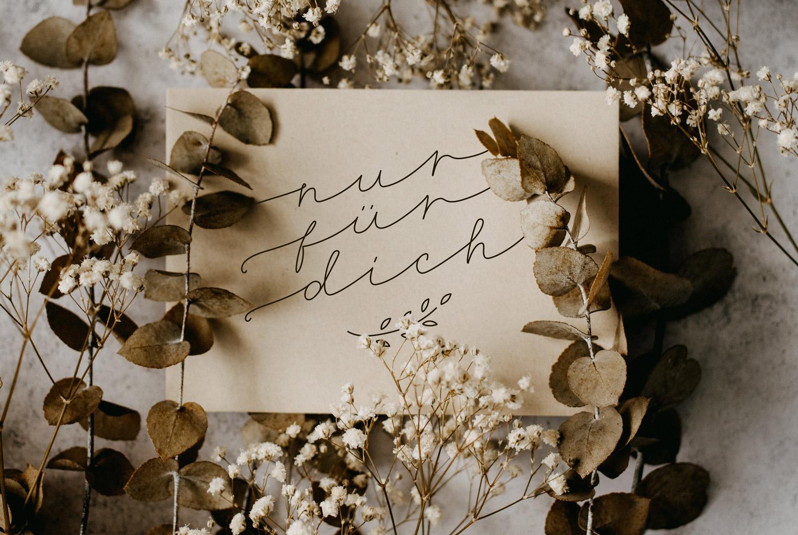Muttertagskarte mit einem Handlettering, umgeben von Blumen