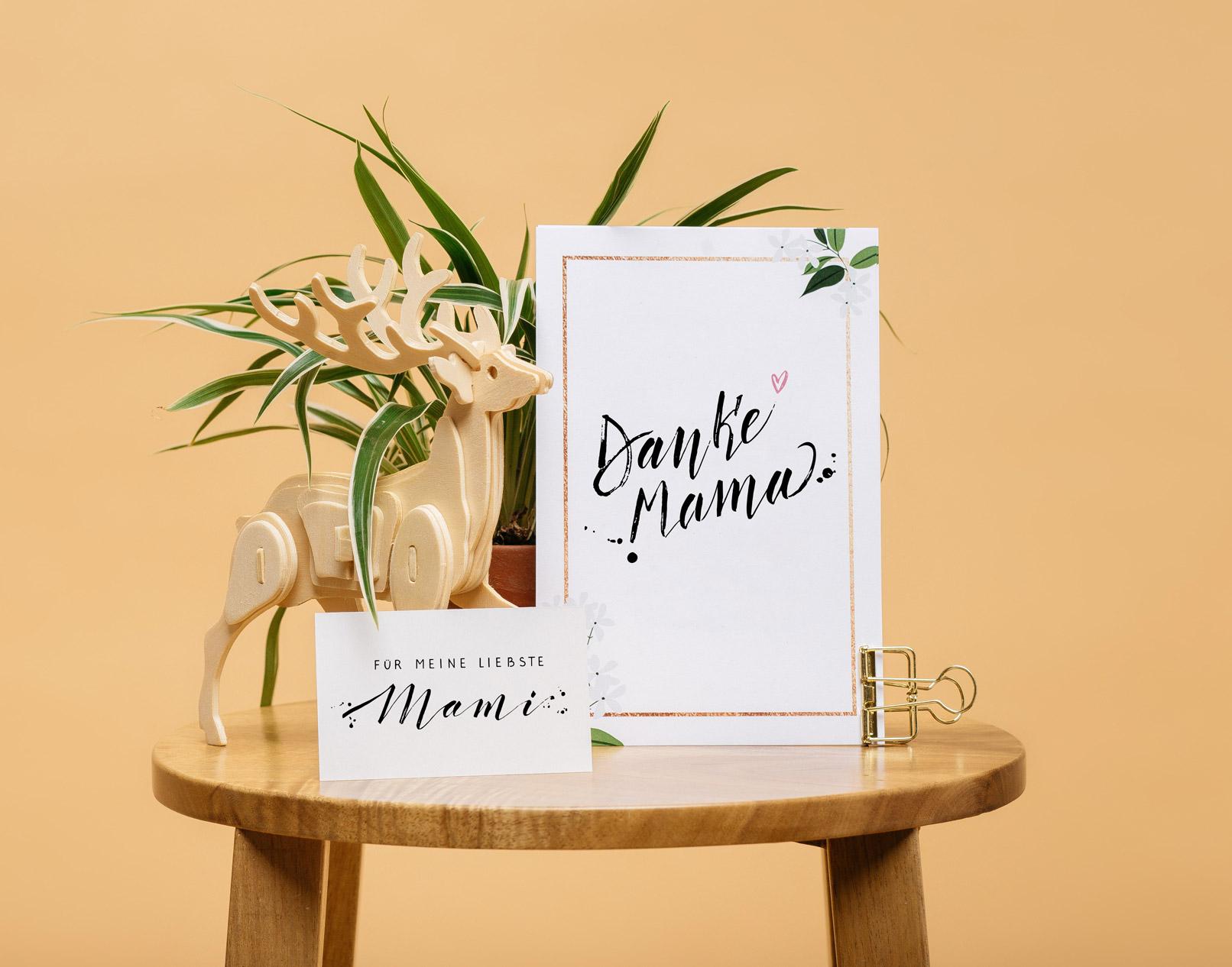 Muttertagskarten mit Handletterings in verschiedenen Größen auf einem Tisch vor Blumen
