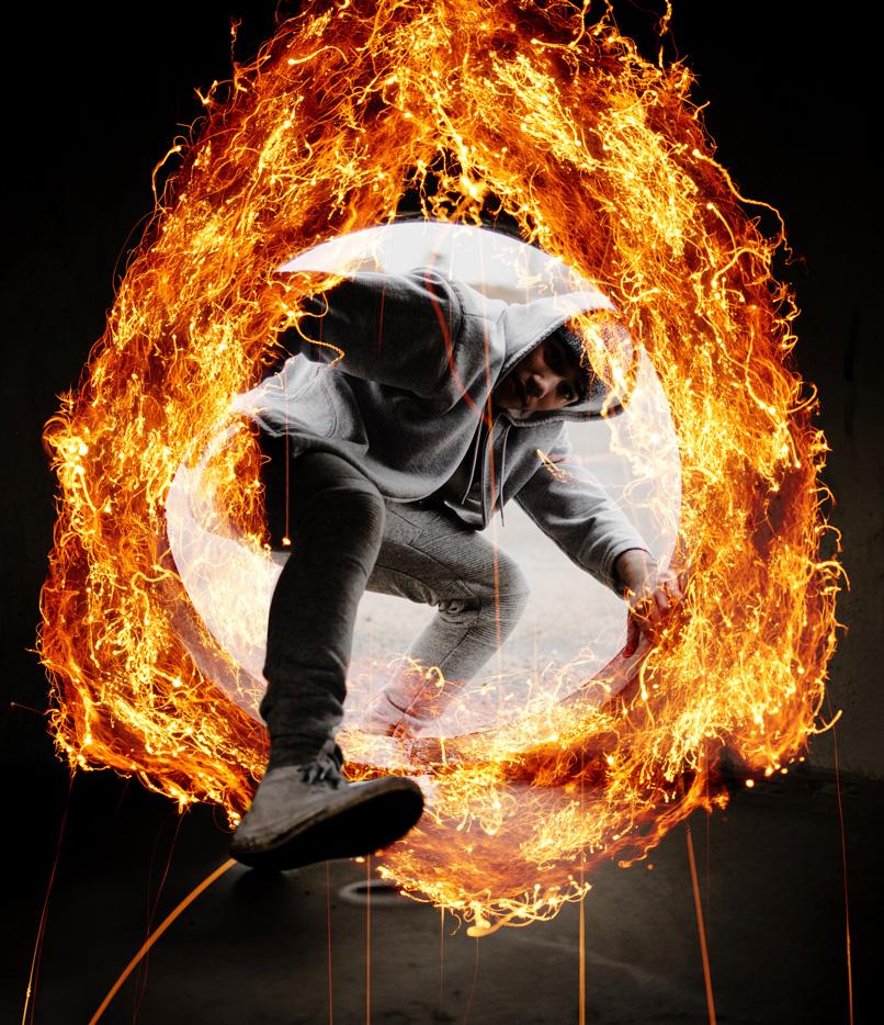 Junger Mann in cooler Pose, umgeben von einem Ring aus Feuer, der mit Feuer-Bildern kreiert wurde.