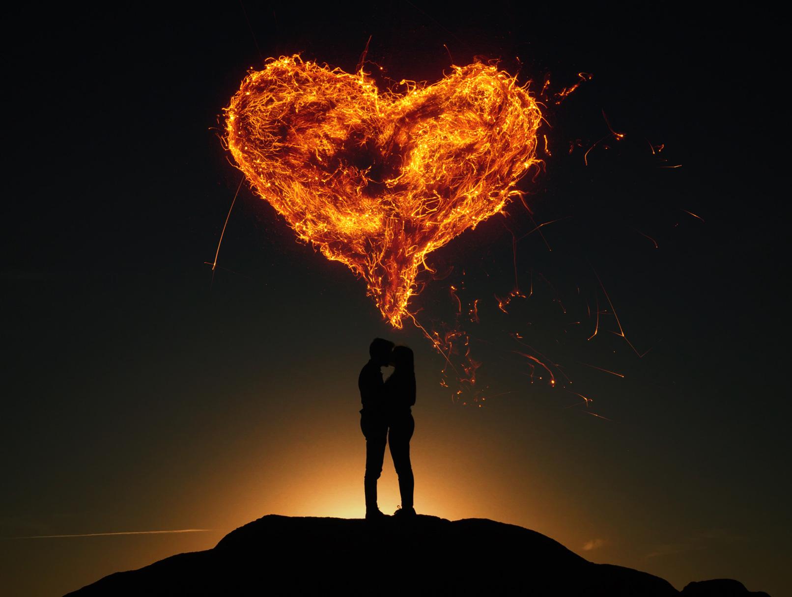 Paar auf einem Hügel im Dunkeln, darüber ein feuriges Herz, erstellt aus Feuer-Texturen.