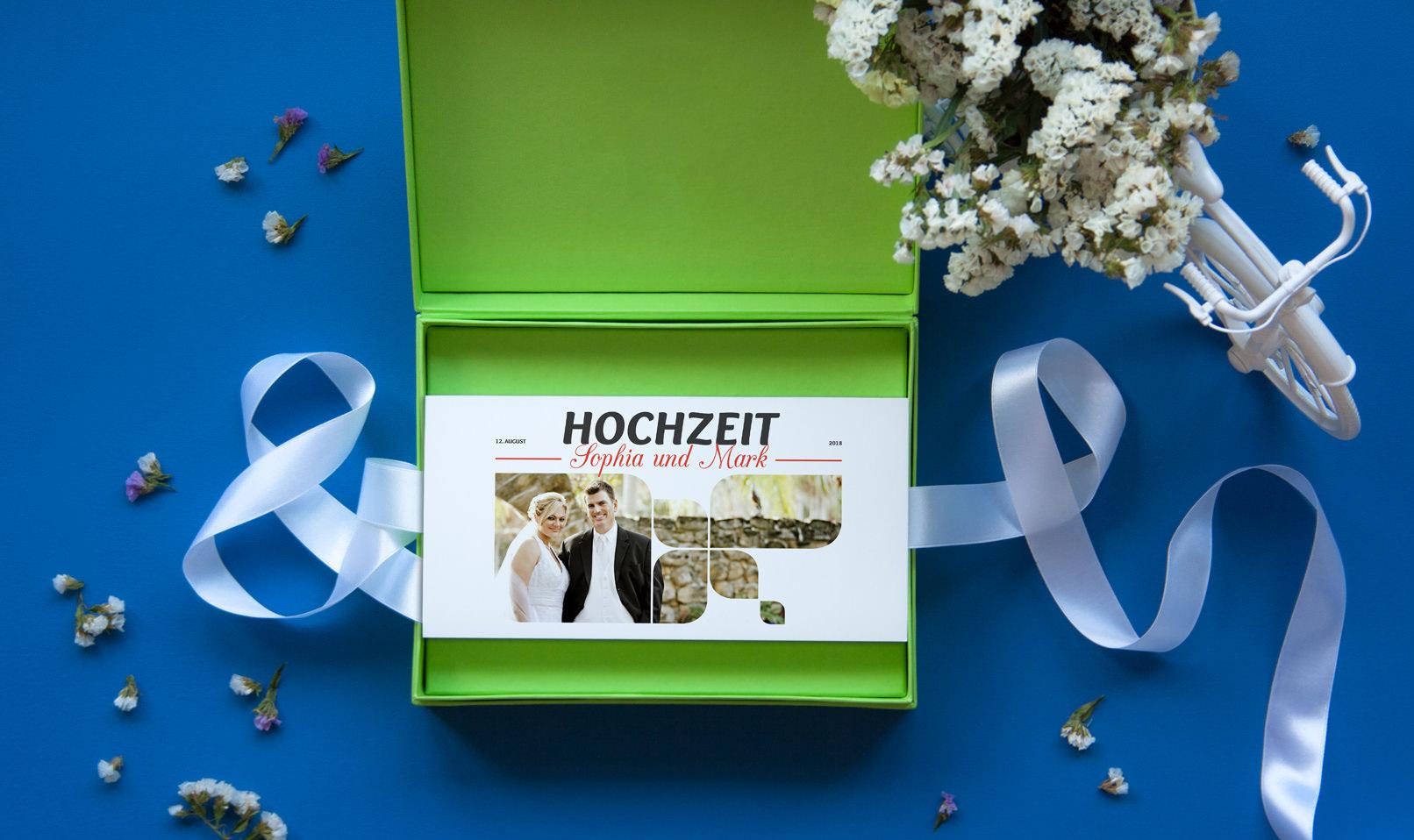 Mockup: Grüne Box mit Hochzeitseinladung, blauer Hintergrund